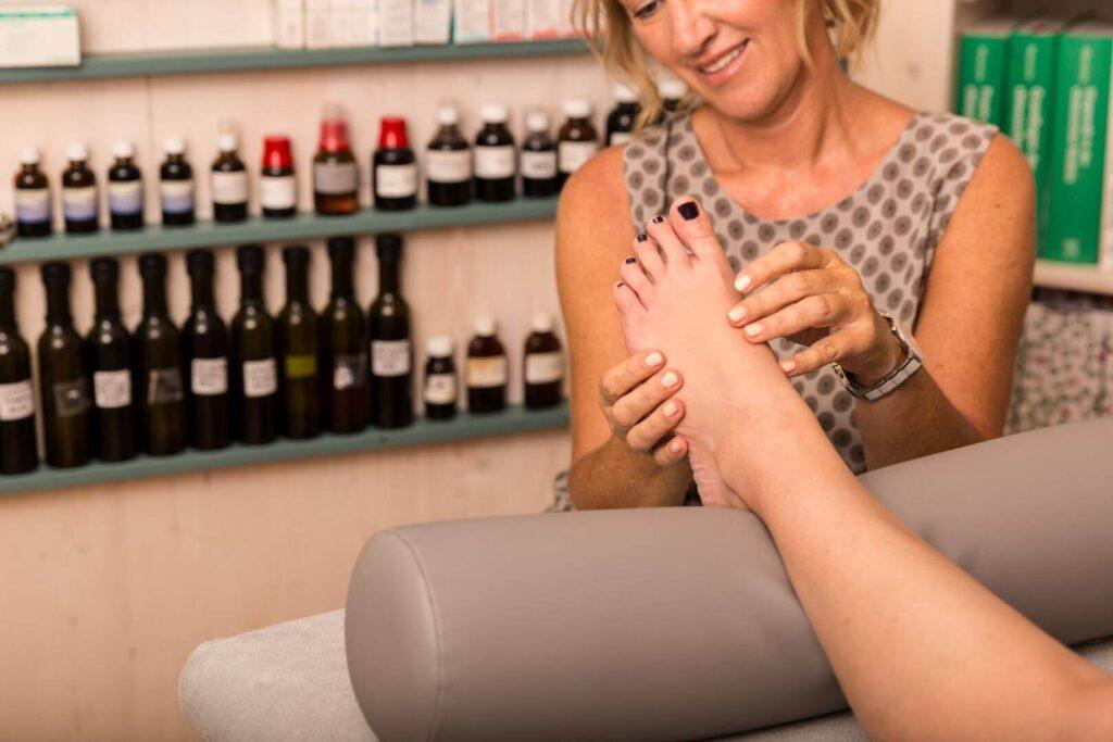 Eine Heilpraktikern führt eine Fuß-Analyse durch